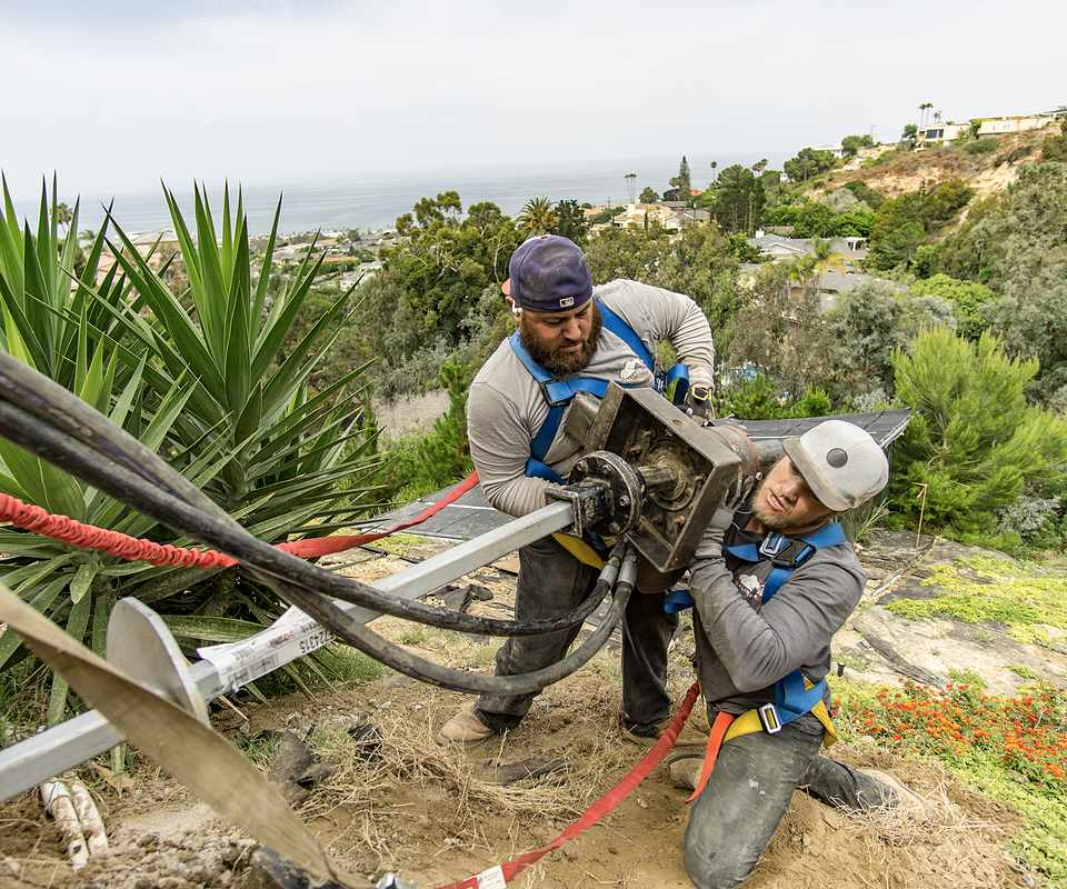 two men stabilizing a slope with helical tieback